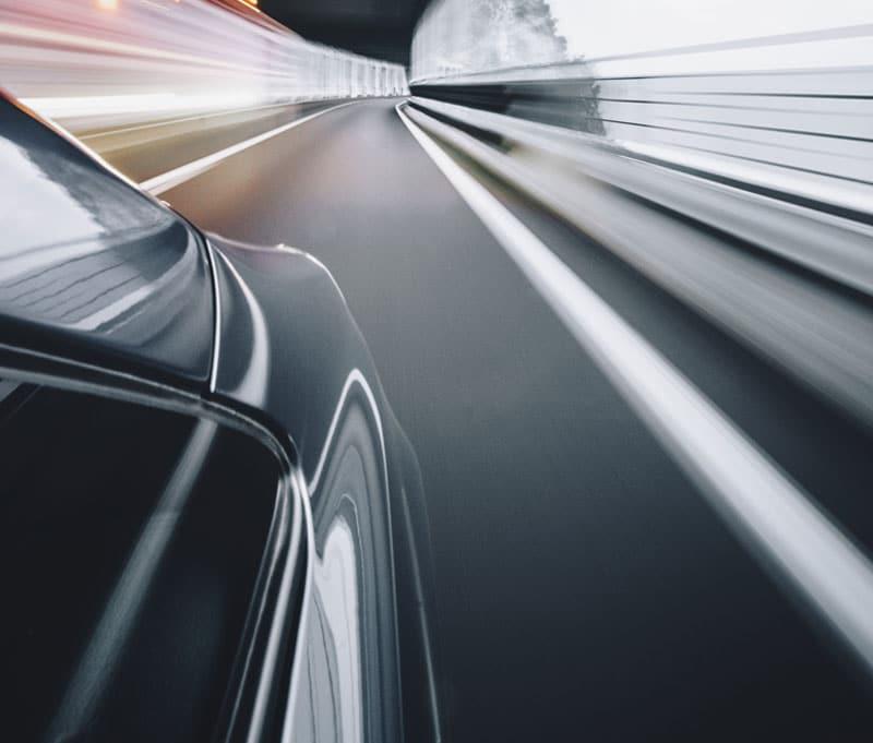 black car speeding down a road